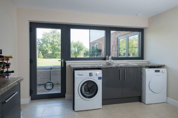 Clean kitchen with bespoke residence 2 door with cat flap with washing machine and tumble dryer