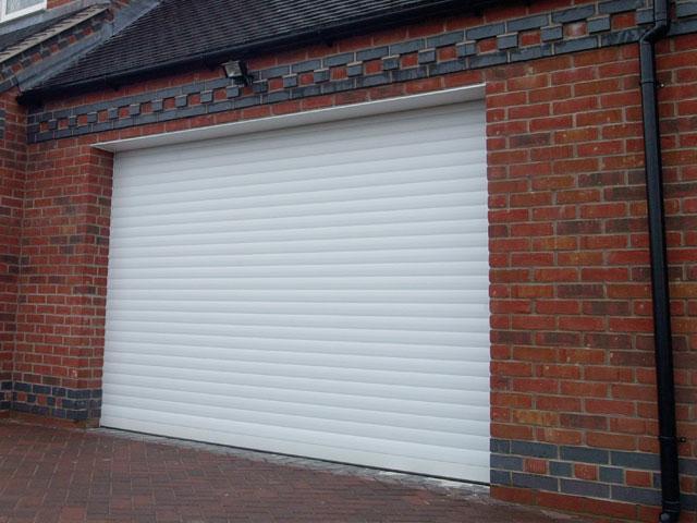 White remote controlled roller garage door title=